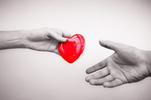 A symbolic gesture of a woman giving a man a cartoon heart, in place of an organ donation.