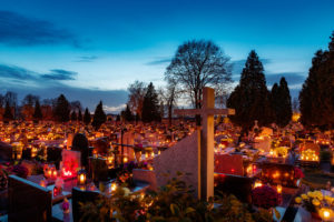 The Day of the Dead in America takes many forms of the traditional celebration. A graveyard adorned with colorful candles and flowers at dusk.