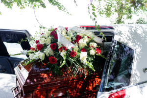 The casket cost increase is likely due to the traditional value we place on ornate funerals. A wreath adorns a casket coming out of a hearse.