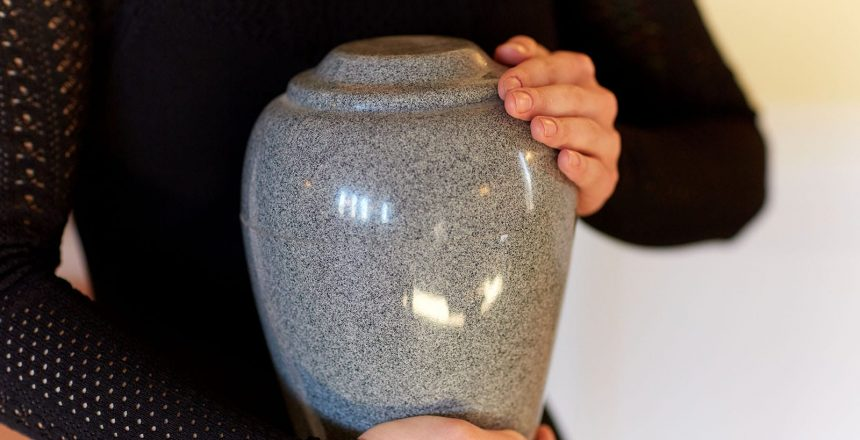 A woman holding a cremation urn. Cremation is an affordable option considering the average funeral cost breakdown.