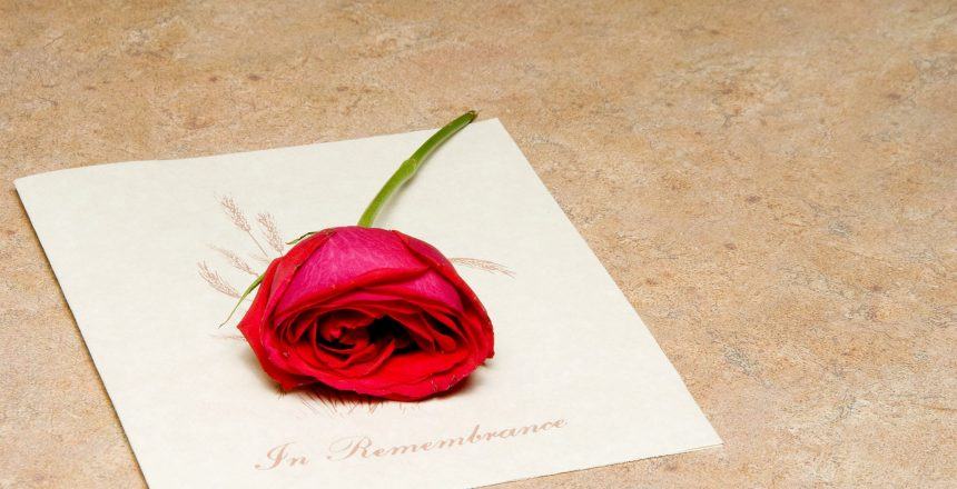 An 'In Remembrance' not you may receive during a funeral visitation, with a red rose on top.