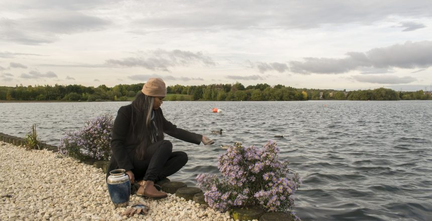 A woman is scattering ashes of a loved one by a Midwestern Lake.