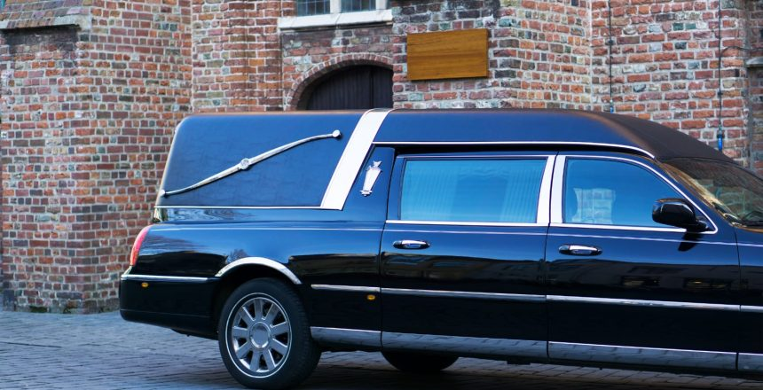 Handling a death away from home will often need travel arrangements for the deceased. A hearse in front of a funeral home.