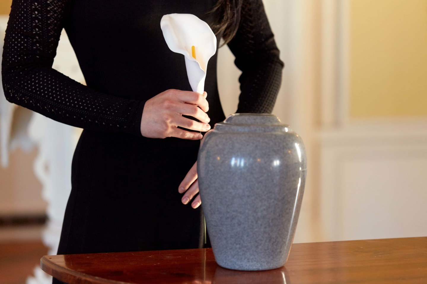 Affordable cremation cost by Simply Cremations. A woman holds a lily next to an urn.